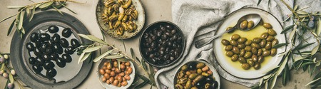 Flat-lay of various kinds of Mediterranean pickled olives in plates and bowls and olive tree branches over grey concrete table background, top view, wide composition. Mediterranean meze appetizer