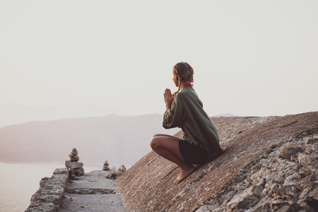 Young woman tourist sitting and meditating on ancient stones of Monolithos castle in Rhodes island, Greece, at sunset on clear summer day