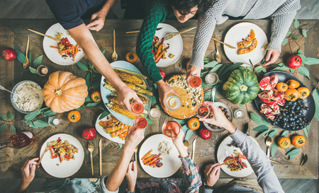 Vegan or vegetarian Thanksgiving, Friendsgiving holiday celebration. Flat-lay of friends eating and clinking glasses at Thanksgiving Day table with pumpkin pie, vegetables, fruit and wine, top view