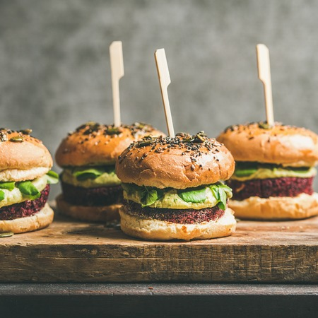 Flat-lay of healthy vegan burgers with quinoa beetroot patties, avocado cream and green sprouts on wooden board, grey wall at background, square crop. Vegetarian, clean eating, alkiline diet food Stock Photo