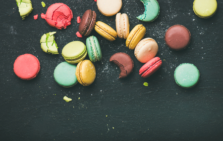 Flat-lay of sweet colorful French macaron cookies over black background, top view, copy space
