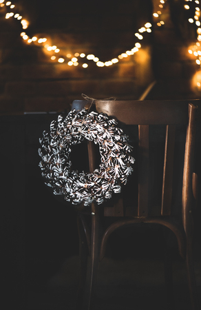 Christmas or New Year holiday low-key style greeting card. White Christmas wreath hanging on back of vintage chair, sparkling garland behind on brick wall. Christmas eve or New Year night mood Stock Photo