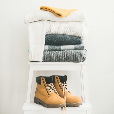 Montón de mantas, bufandas y suéteres, gorra y botas de punto gris y blanco cálido para el invierno o el otoño en un taburete blanco cerca de la pared blanca, espacio de copia, cultivo cuadrado. Acogedor ambiente de invierno en casa