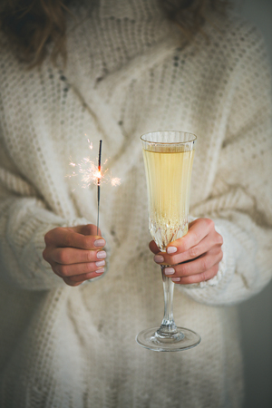 Christmas or New Year celebration concept. Woman in white woolen sweater holding glass of champagne and sparkler in hands, close-up Banco de Imagens