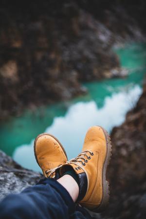 Pieds de voyageur ou d'explorateur de la nature sauvage en bottes de randonnée jaunes sales sur un gouffre avec canyon de la rivière de montagne en arrière-plan. Concept de voyage, de tourisme, de voyage ou d'aventure Banque d'images