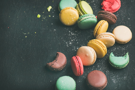 Sweet colorful French macaroon cookies variety with sugar powder over black background, top view, selective focus, copy space Stock Photo