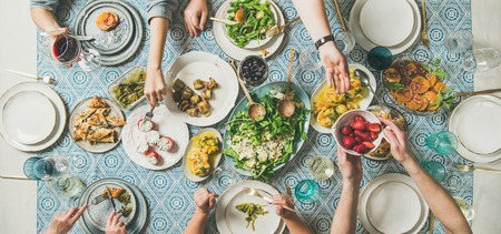 Mediterranean style dinner. Flat-lay of table with salad, starters, pastries over blue table cloth with hands holding drinks, sharing food, top view, wide composition. Holiday vegetarian party concept 写真素材