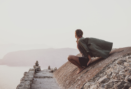 Young woman tourist sitting and looking at horizon on ancient stones of Monolithos castle in Rhodes island, Greece