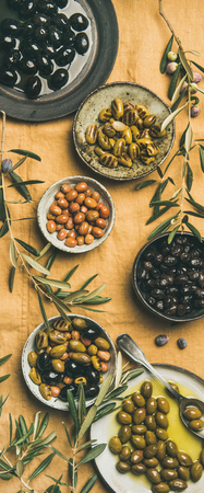 Flat-lay of various kinds of Mediterranean pickled olives in plates and bowls and olive tree branches on yellow linen