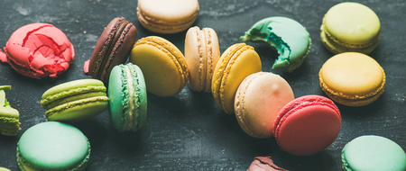 Sweet colorful French macaroon cookies dessert variety over black 写真素材