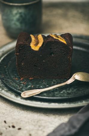 Piece of freshly baked dark chocolate banana bread cake dessert on grey plate over concrete table