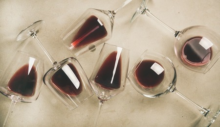 Flat-lay of red wine in glasses over grey concrete 写真素材