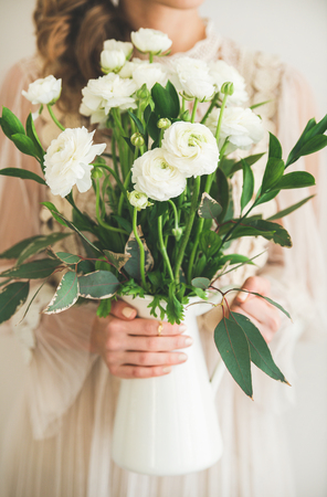 Spring white buttercup flowers in white enamel jug in hands of woman. Stock Photo