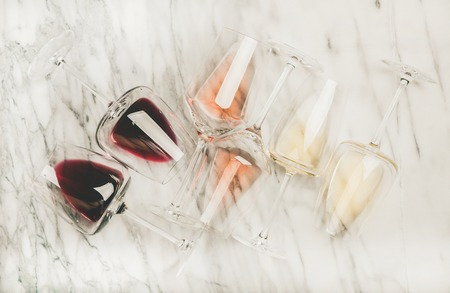 Flat-lay of red, rose and white wine in glasses over grey marble