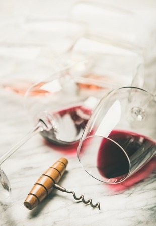 Red and rose wine in glasses and corkscrew over grey marble Stock Photo