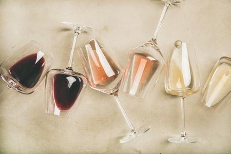 Flache Lage von Rot-, Rosé- und Weißwein in Gläsern über grauem Beton