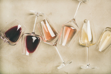 Flat-lay of red, rose and white wine in glasses over grey concrete