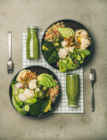 Healthy dinner, lunch setting. Flat-lay of vegan superbowls or Buddha bowls with hummus, vegetables, fresh salad, beans, couscous and avocado and green smoothies in bootles, top view. Vegetarian food Stock Photo