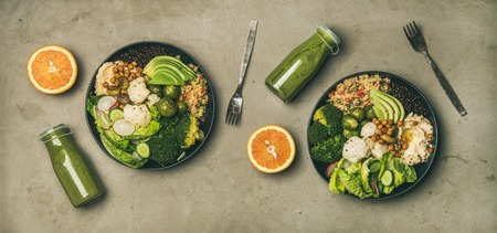 Healthy dinner, lunch setting. Flat-lay of vegan superbowls or Buddha bowls with hummus, vegetables, fresh salad, beans, couscous, avocado and green smoothies in bootles, top view. Vegetarian food