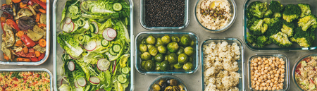 Healthy vegan dishes in containers. Flat-lay of vegetable salad, legumes, beans, olives, sprouts, hummus dip, couscous for take-away lunch, top view, wide composition. Spring menu, dieting food concep