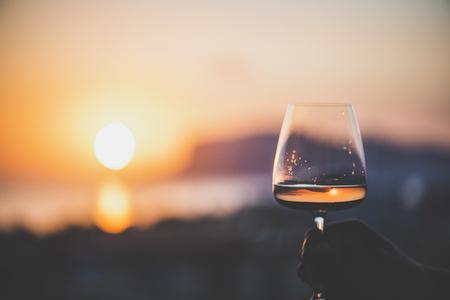 La main de l'homme tenant un verre de vin rosé et avec la mer et un beau coucher de soleil en arrière-plan, gros plan, composition horizontale. Concept d'ambiance détendue de soirée d'été