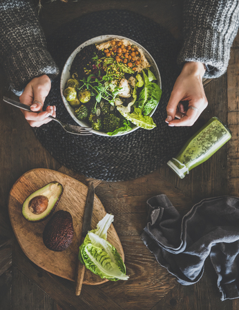 Healthy dinner or lunch setting. Flat-lay of vegan superbowl or Buddha bowl with hummus, vegetables, fresh salad, beans, couscous and avocado, green smoothie and womans hands over table, top view Stock Photo