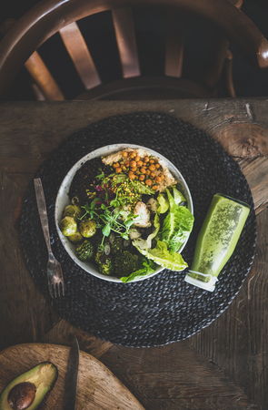 Healthy dinner or lunch setting. Flat-lay of vegan superbowl or Buddha bowl with hummus, vegetables, fresh salad, beans, couscous and avocado and green smoothie on table, top view