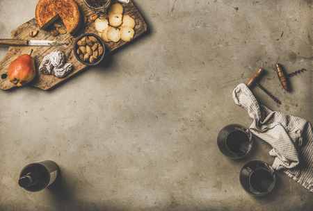 Wine and snack set. Flat-lay of wine bottle, two glasses of red wine, vintage corkscrews, cheese and appetizers on board over dusty concrete background, top view, copy space. Party food concept
