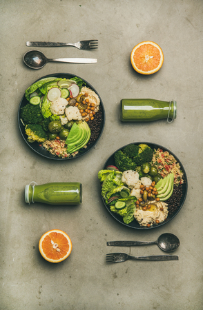 Healthy dinner, lunch setting. Flat-lay of vegan superbowls or Buddha bowls with hummus, vegetable, salad, beans, couscous, avocado and green smoothies, top view. Clean eating, vegetarian food concept