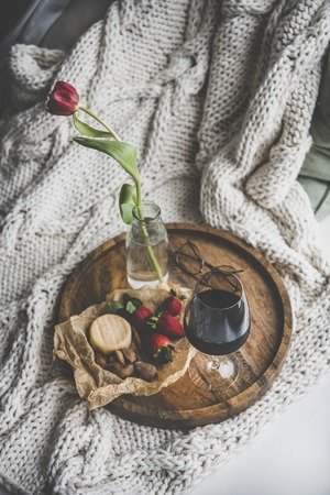 Wine snack set with flowers. Glass of red wine, cheese, roasted almonds, strawberries and Spring red tulip in jar on wooden tray over white knitted blanket. Relaxed or romantic mood concept Фото со стока