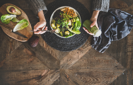 Healthy dinner, lunch setting. Flat-lay of vegan superbowl or Buddha bowl with hummus, vegetable, salad, beans, couscous and avocado, smoothie and womans hands over wooden table, top view, copy space Stock Photo