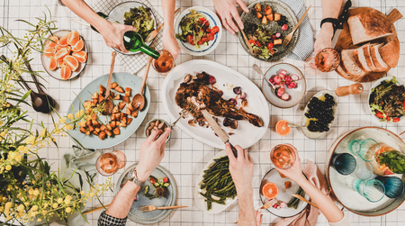 Family or friends gathering dinner. Flat-lay of hands of people eating