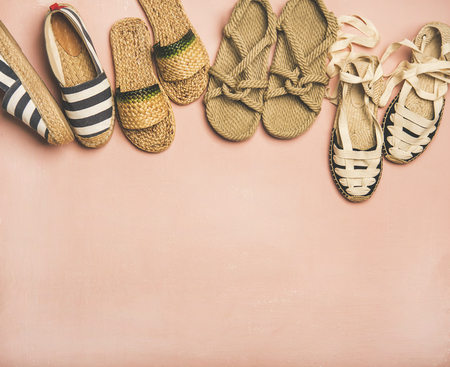 Variety of trendy woman summer shoes. Flat-lay of espadrilles, sandals, flip flops made of natural materials over pastel pink