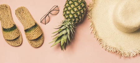 Summer apparel items. Flat-lay of summer flip flops, sunglasses, straw sunhat and fresh pineapple over pastel pink