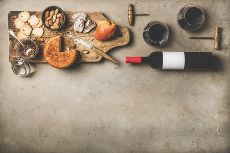 Wine and snack set. Flat-lay of wine bottle with blank label, vintage corkscrews, glasses with wine, cheese and appetizers on board over concrete Stock Photo