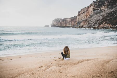 Young woman tourist sitting at Atlantic ocean sandy beach in Nazare, Portugal