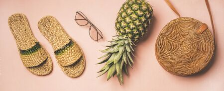 Variety of summer apparel items. Flat-lay of summer flip flops, sunglasses, wicker shoulder bag and pineapple over pastel pink 写真素材