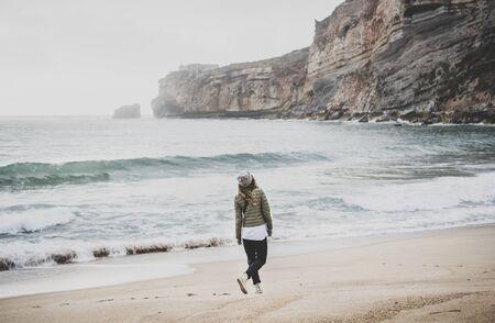 Young woman tourist walking at Atlantic ocean sandy beach