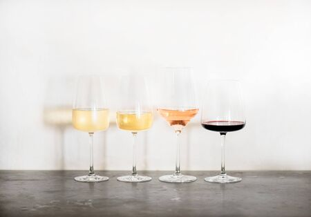 Variety of wine types. Light and full-bodied white, rose and red wine in glasses in row over concrete table, white wall