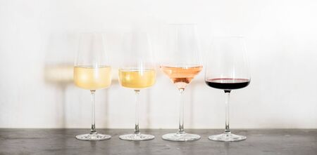 Variety of wine types. Light and full-bodied white, rose and red wine in glasses in row over concrete table