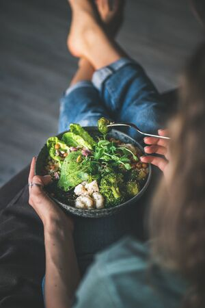 Healthy dinner or lunch. Curly woman in t-shirt and jeans sitting at home and eating vegan super bowl Stock Photo