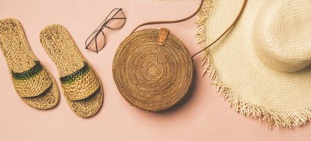 Summer apparel items. Flat-lay of summer flip flops, sunglasses, straw sunhat and wicker round shoulder bag over pastel