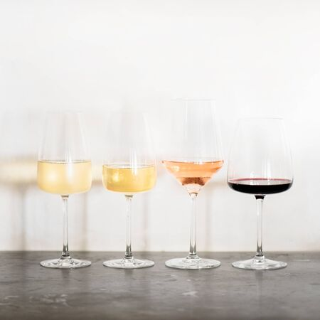 Variety of wine types. Light and full-bodied white, rose and red wine in glasses in row over concrete table, white wall background, copy space. Wine list, wine boutique or degustation, square crop Stockfoto