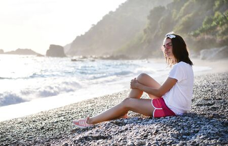 Beautiful young woman in summer look and sunglasses is smiling and relaxing at pebble wild beach at Mediterranean sea. Traveling, tourism, vacation, freedom, slow living concept