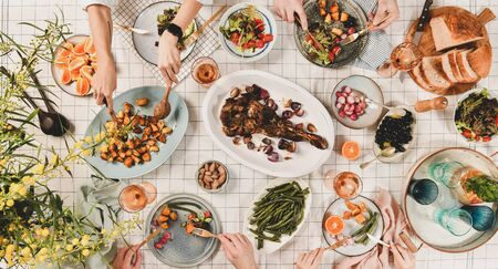 Family, friends gathering dinner. Flat-lay of peoples hands over table with roasted lamb shoulder, salads, vegetables, snacks, rose wine and mimosa branches, top view, wide composition 写真素材