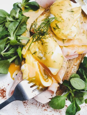 Trendy breakfast. Flat-lay of poached Eggs Benedict on sourdough bread toast with green salad and pork ham on white plate, close-up, top view Stock Photo