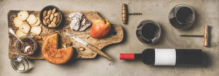Wine and snack set. Flat-lay of wine bottle with blank label, corkscrews, glasses with wine, cheese and appetizers on board over concrete background, top view, wide composition. Party food concept