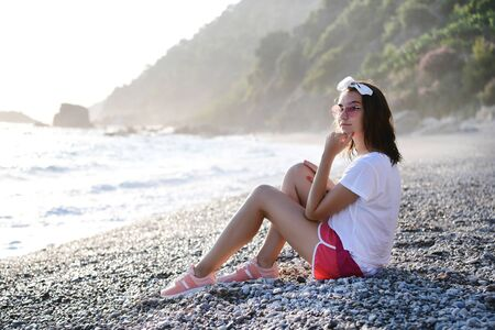 Beautiful young woman in summer look and sunglasses is dreaming and relaxing at pebble wild beach at Mediterranean sea. Traveling, tourism, vacation, freedom, slow living concept