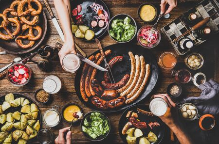 Flat-lay of Octoberfest dinner table concept with grilled sausages, pretzel pastry, potatoes, cucumber salad, sauces, beers and people drinking and eating over dark wooden background, top view 免版税图像