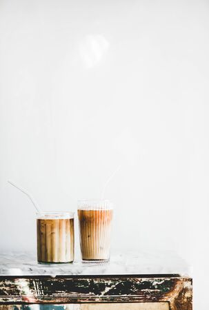 Homemade iced latte coffee in glasses with straws on grey marble table, white wall at background, copy space, vertical composition. Summer cold refreshing drink concept